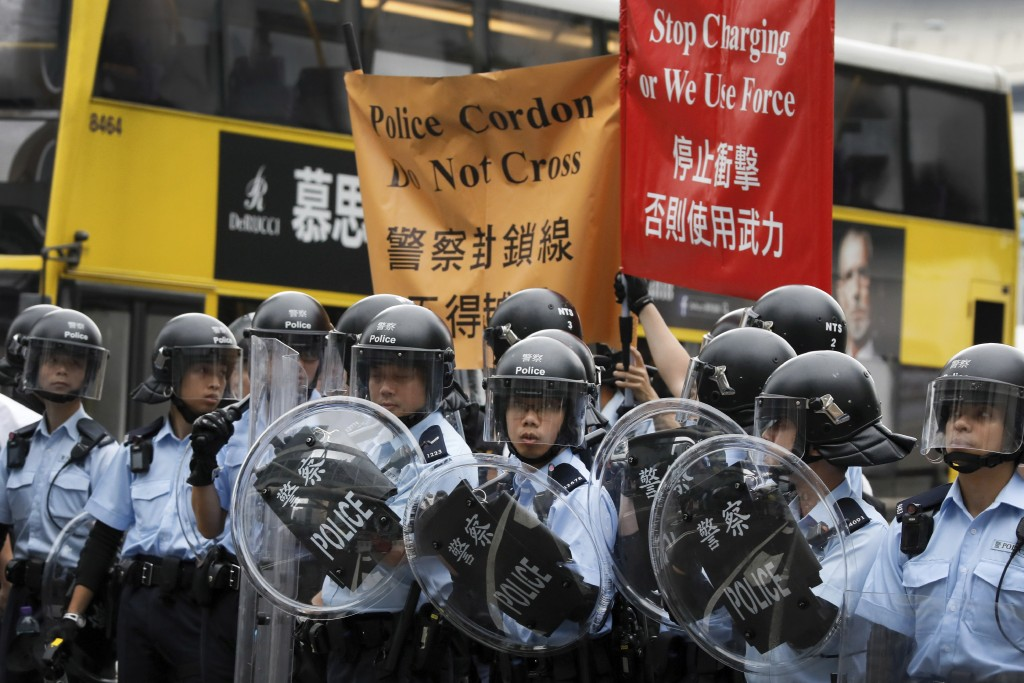 In this June 12, 2019, file photo, police line a perimeter as they watch the protesters near the Legislative Council in Hong Kong. (AP Photo/Vincent Y