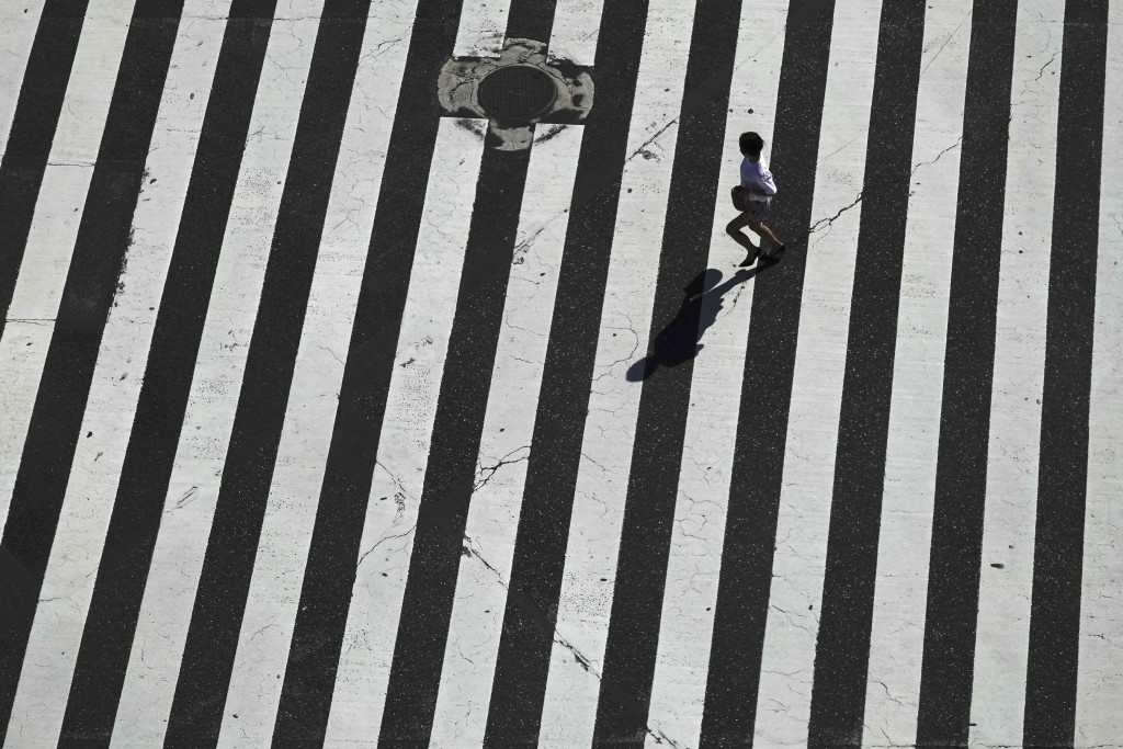 A woman runs across the famous Shibuya crossing Thursday, June 13, 2019, in Tokyo. It's not just a crossing. Located just outside Shibuya Station, the
