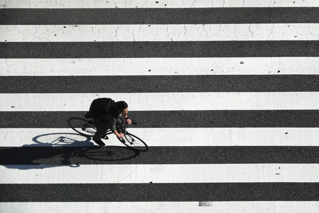 A man rides his bike across the famous Shibuya crossing Thursday, June 13, 2019, in Tokyo. It's not just a crossing. Located just outside Shibuya Stat