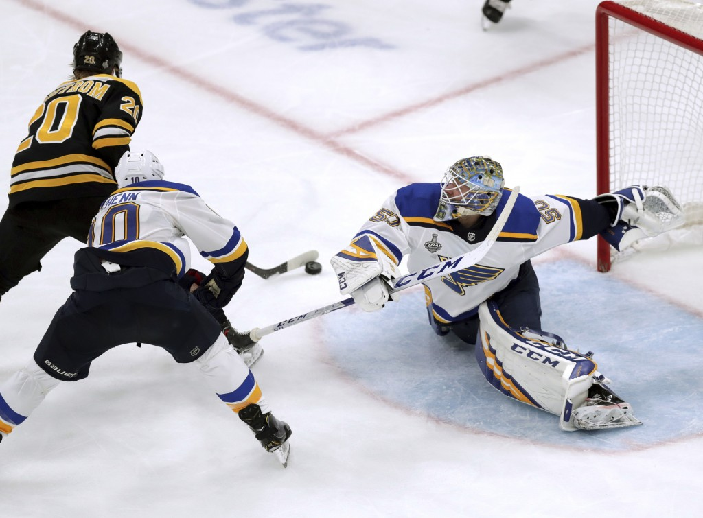 St. Louis Blues goaltender Jordan Binnington, right, stretches to make a save against Boston Bruins' Joakim Nordstrom (20), of Sweden, during the thir...
