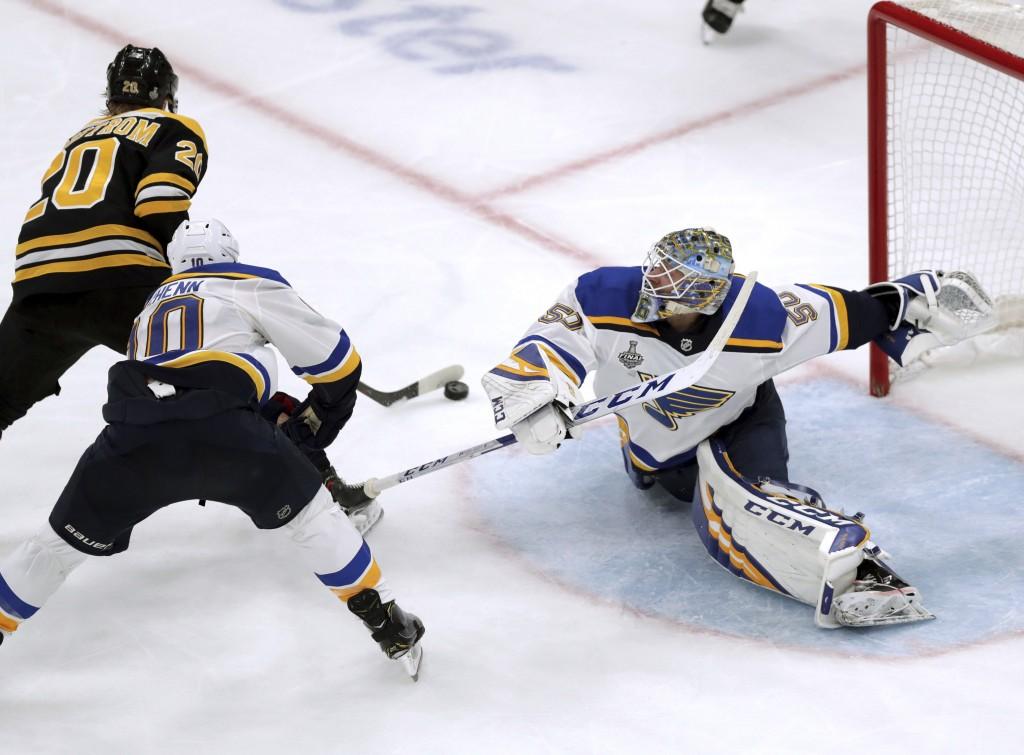 St. Louis Blues goaltender Jordan Binnington, right, stretches to make a save against Boston Bruins' Joakim Nordstrom (20), of Sweden, during the thir