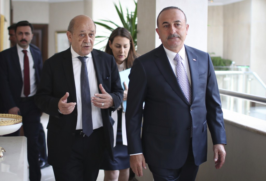 French Foreign Minister Jean-Yves Le Drian, left, and Turkey's Foreign Minister Mevlut Cavusoglu arrive for a meeting in Ankara, Turkey, Thursday, Jun