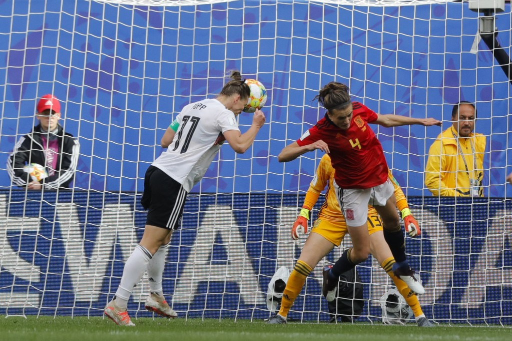 Germany's Alexandra Popp, left, heads the ball against Spain's Irene Paredes, right, and Spain goalkeeper Sandra Panos, background, before teammate Ge