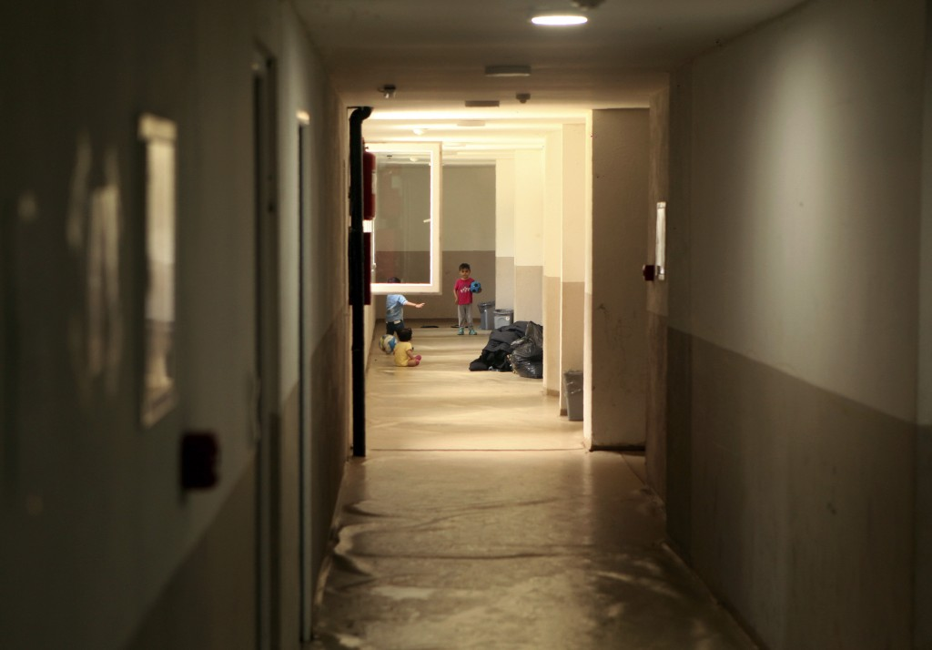 In this photo taken Tuesday, June 11, 2019, children play in the hallway of the abandoned building, now serving as a shelter in the northwestern Bosni
