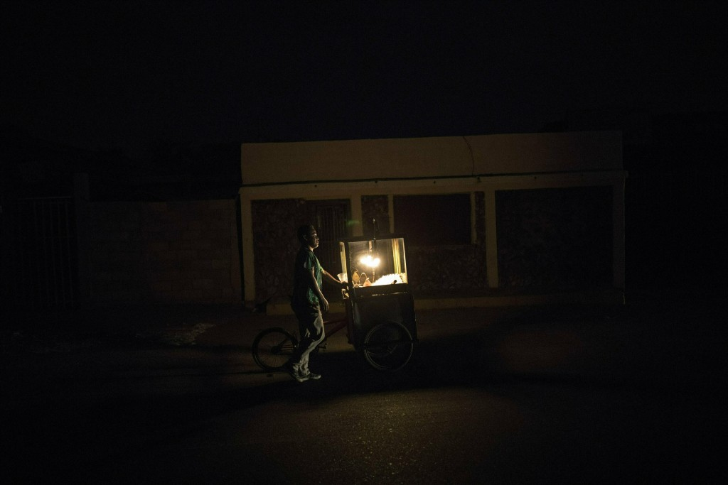 In this May 15, 2019 photo, popcorn vendor Raul Navas looks for customers during a black out in Maracaibo, Venezuela. Navas uses a kerosene lamp to il
