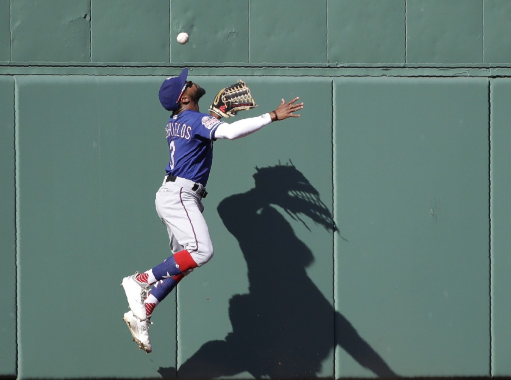 Texas Rangers center fielder Delino DeShields cannot make the catch on an RBI-triple off the wall by Boston Red Sox's Andrew Benintendi in the third i