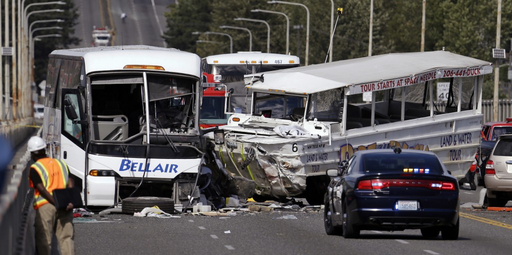 "FILE - In this Sept. 24, 2015 file photo, a ""Ride the Ducks"" amphibious tour bus, right, and a charter bus remain at the scene of a multiple fatality"