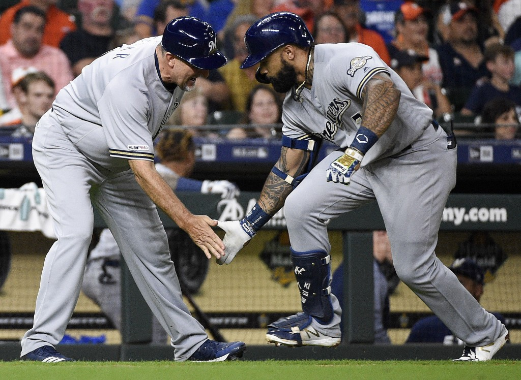 Milwaukee Brewers' Eric Thames, right, celebrates his game-tying solo home run off Houston Astros starting pitcher Justin Verlander with third base co