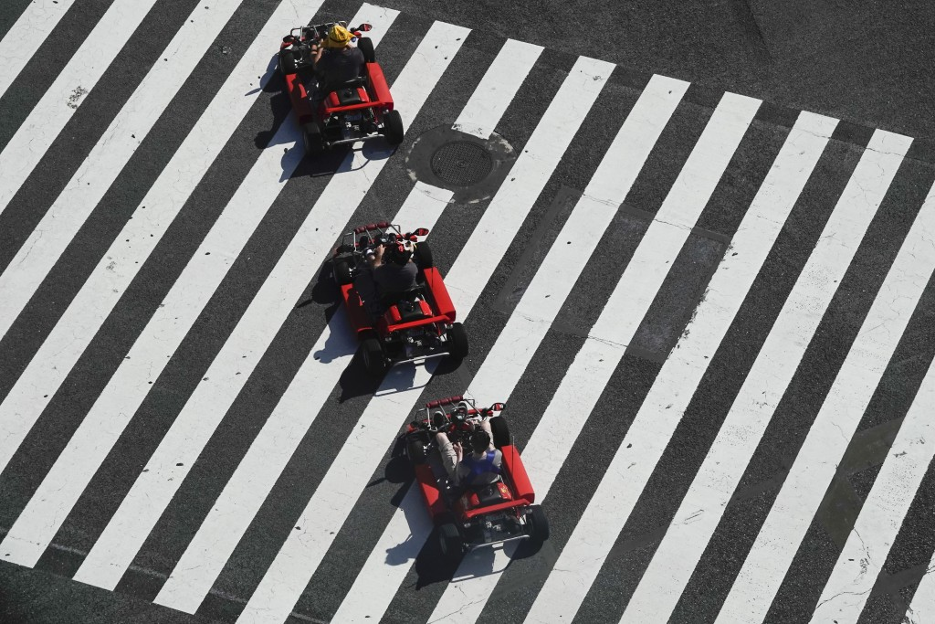 A group of people in go-karts cruise through the Shibuya crossing Thursday, June 13, 2019, in Tokyo. It's not just a crossing. Located just outside Sh