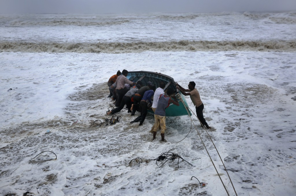 People try to move a fishing boat to a safer ground on the Arabian Sea coast in Veraval, Gujarat, India, Thursday, June 13, 2019. Authorities have eva