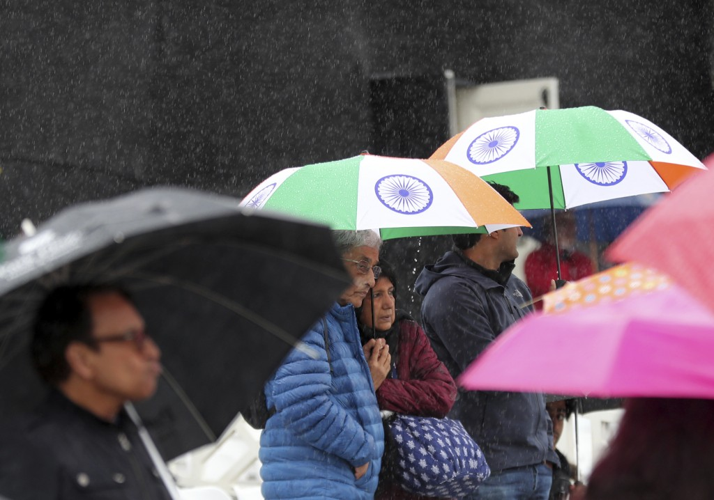 Indian fans stand under umbrellas as it rains delaying start of the Cricket World Cup match between India and New Zealand at Trent Bridge in Nottingha