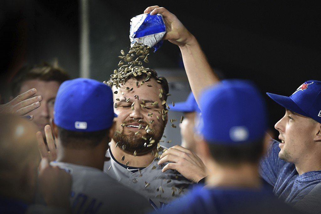 Toronto Blue Jays' Rowdy Tellez, center, has sunflower seeds poured over him in the dugout after hitting a grand slam against the Baltimore Orioles du...