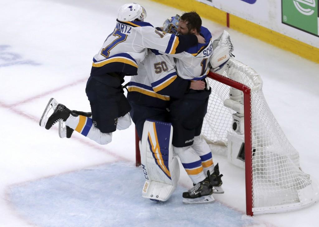 St. Louis Blues' Jaden Schwartz, left, and Brayden Schenn, right, mob goaltender Jordan Binnington, to celebrate their win over the Boston Bruins in G