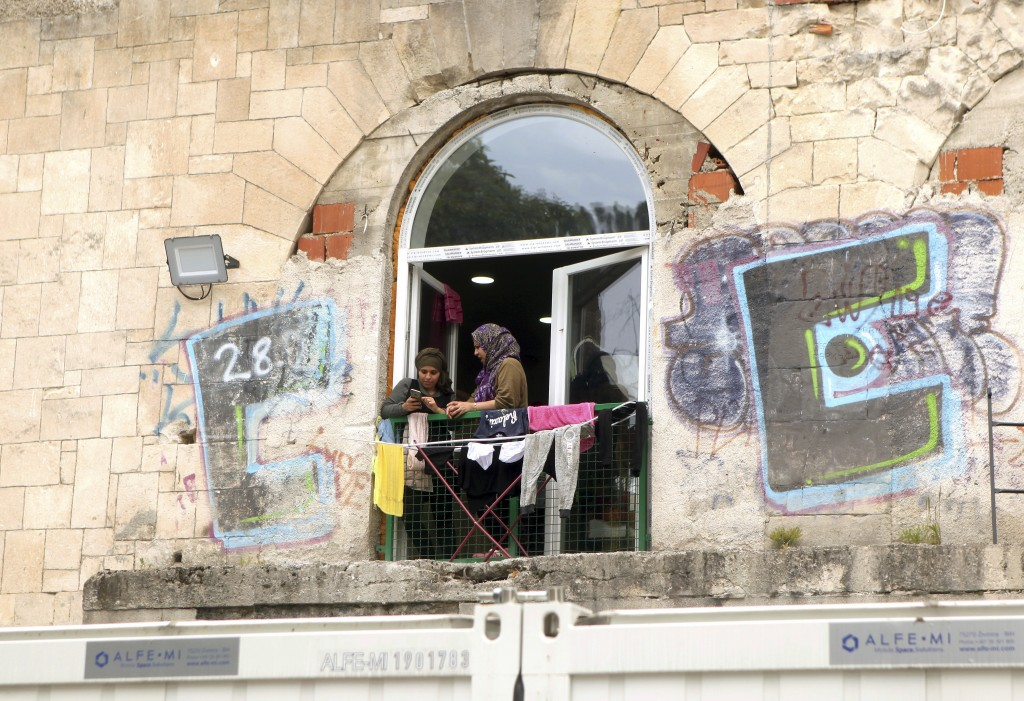 In this photo taken Tuesday, June 11, 2019, two migrant women talk on the window of the abandoned building, now serving as a shelter in the northweste