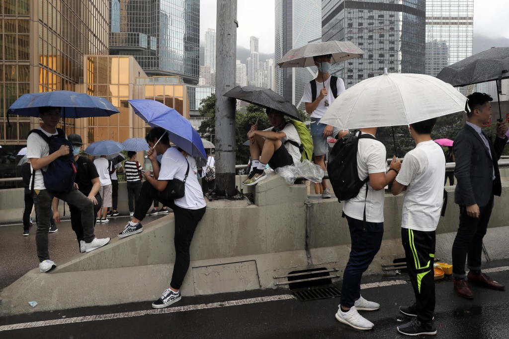 In this photo taken on Wednesday, June 12, 2019, protestors use umbrellas for cover as they gather near the Legislative Council in Hong Kong. Young Ho