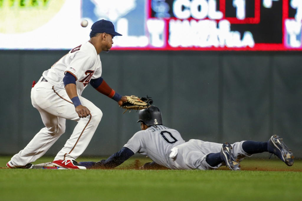 Seattle Mariners' Mallex Smith steals second base as Minnesota Twins shortstop Jorge Polanco misses the ball on a throwing error by catcher Mitch Garv