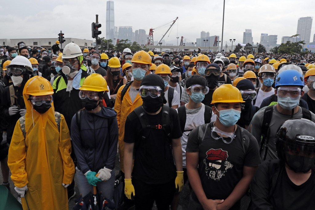 In this photo taken on Wednesday, June 12, 2019, protestors wear masks and helmets to protect their identities near the Legislative Council in Hong Ko