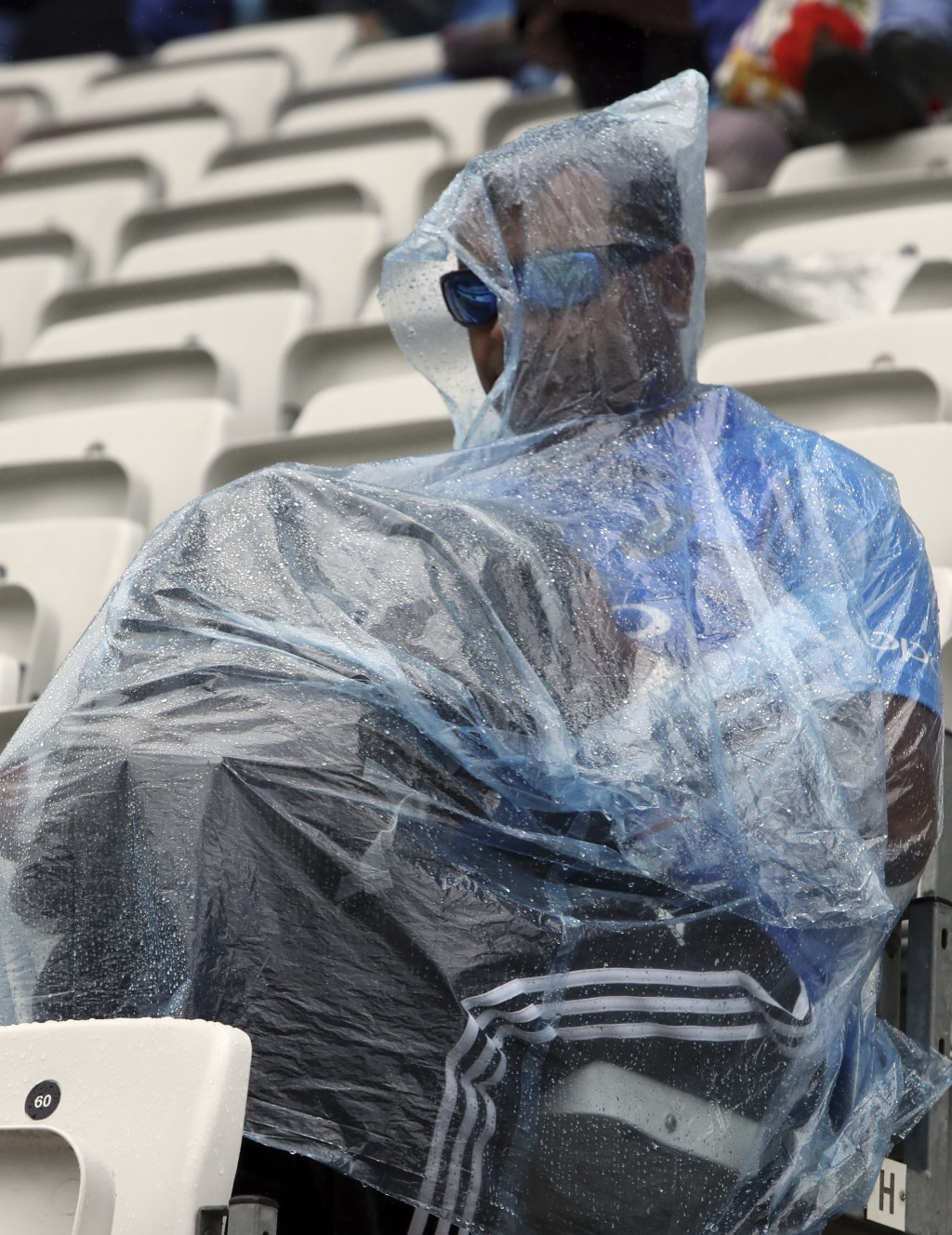 A spectator shelters from the rain as play is delayed due to rain for the Cricket World Cup match between India and New Zealand at Trent Bridge in Not