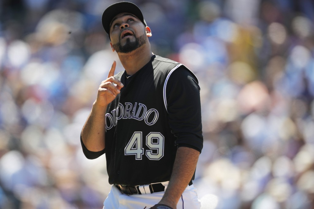 Colorado Rockies starting pitcher Antonio Senzatela gestures as he heads to the dugout after giving up a walk to Chicago Cubs' Victor Caratini in the ...