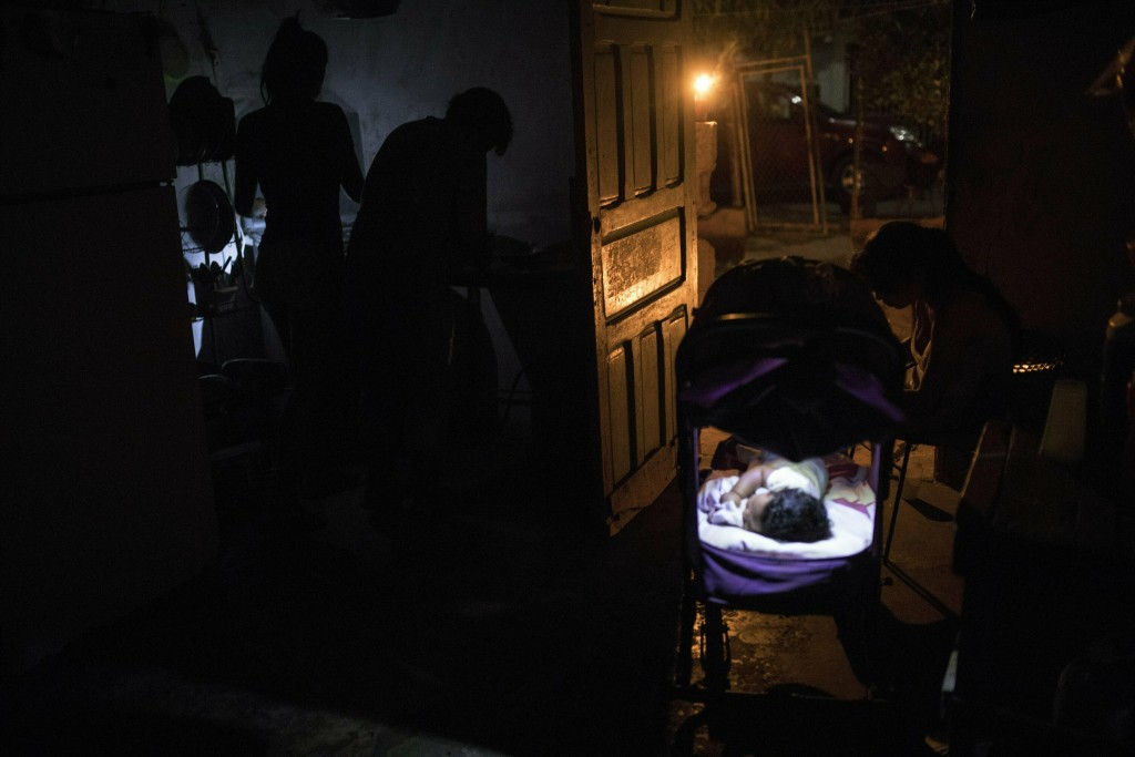 In this May 15, 2019 photo, the Zabala family prepares dinner at their home during a black out in Maracaibo, Venezuela. Venezuela's current President