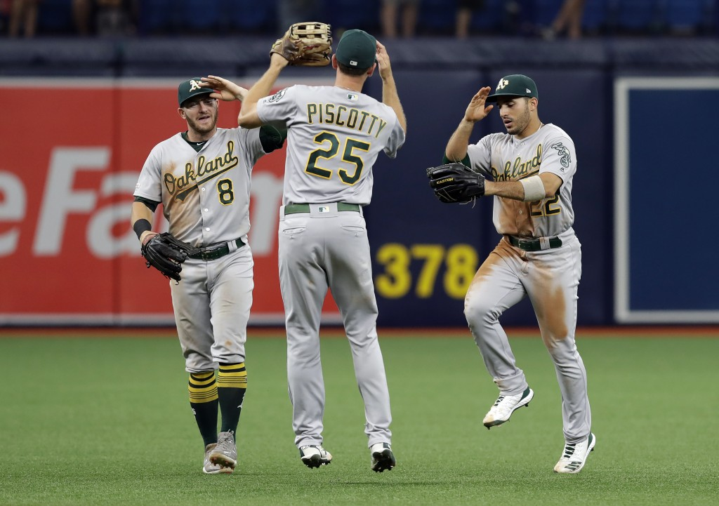 Oakland Athletics center fielder Ramon Laureano (22), right fielder Stephen Piscotty (25) and left fielder Robbie Grossman (8) celebrate after the tea