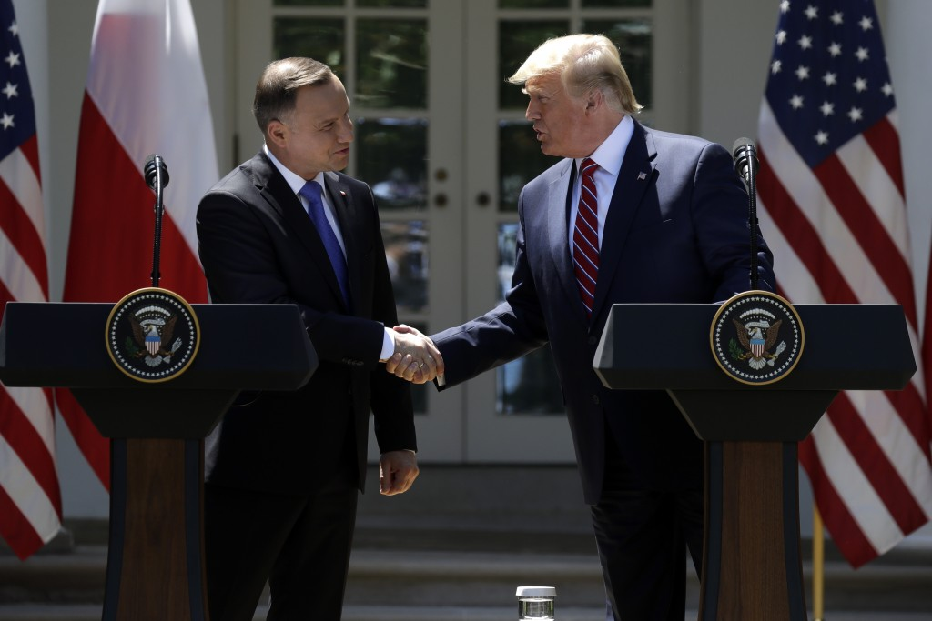 President Donald Trump shakes hands with Polish President Andrzej Duda during a news conference in the Rose Garden of the White House, Wednesday, June