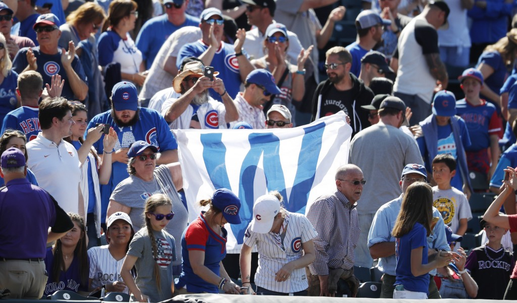 Fans hoist the flag to signify a victory for the Chicago Cubs, after the team's baseball game against the Colorado Rockies on Wednesday, June 12, 2019...