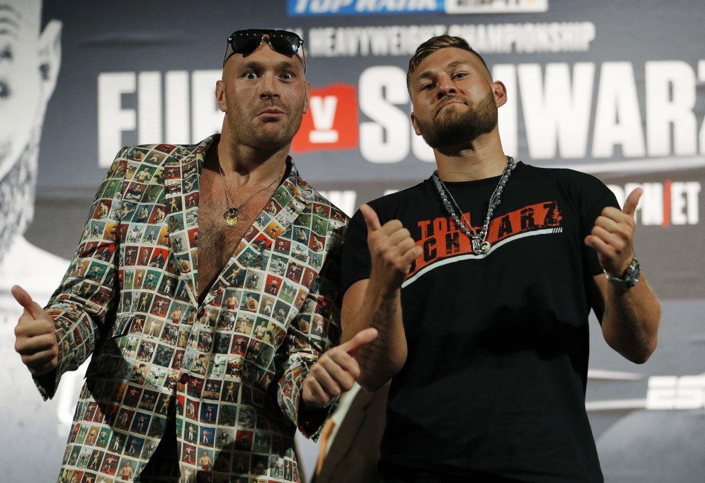 Tyson Fury, left, of England, and Tom Schwarz, of Germany, pose for photographers during a news conference for their upcoming fight Wednesday, June 12...