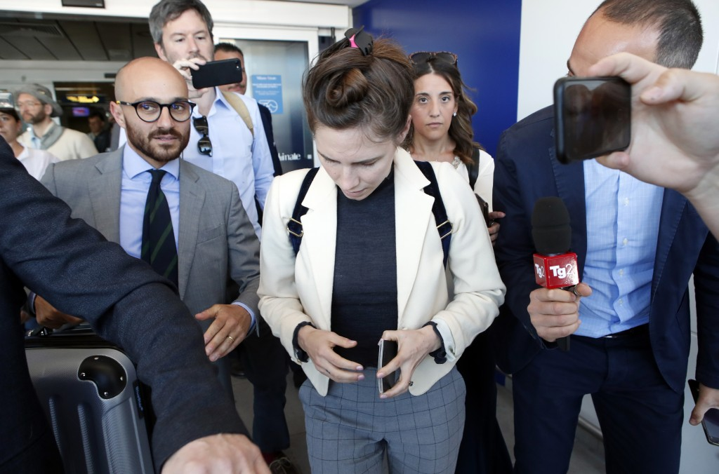 Amanda Knox, center, is approached by journalists upon her arrival in Linate airport, Milan, Italy, Thursday, June 13, 2019. Knox has returned to Ital