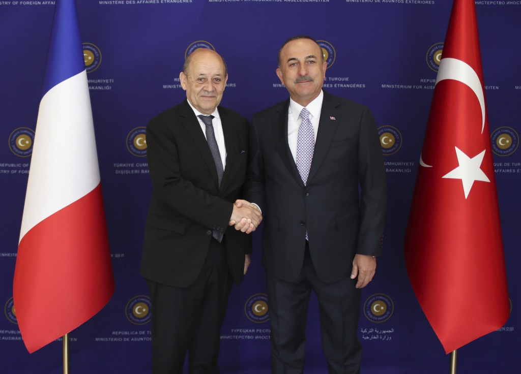 French Foreign Minister Jean-Yves Le Drian, left, and Turkey's Foreign Minister Mevlut Cavusoglu shake hands before a meeting in Ankara, Turkey, Thurs