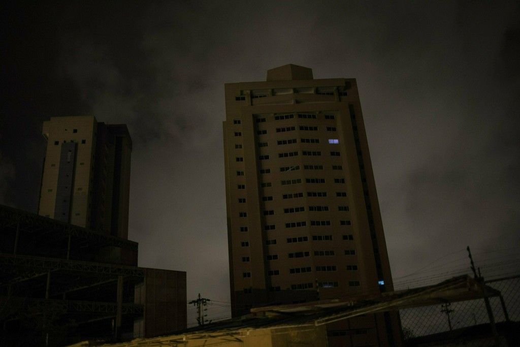 In this May 23, 2019 photo, only two apartments of a building are illuminated by electric generators during a black out in Maracaibo, Venezuela. Some