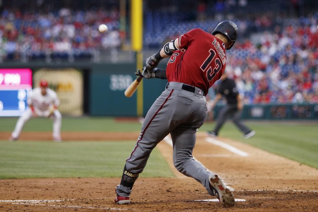 Arizona Diamondbacks' Nick Ahmed hits an RBI sacrifice fly off Philadelphia Phillies starting pitcher Zach Eflin during the fifth inning of a baseball