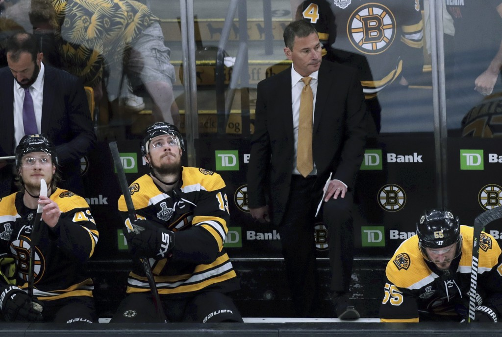Boston Bruins head coach Bruce Cassidy watches from behind the bench during the first period in Game 7 of the NHL hockey Stanley Cup Final, Wednesday,