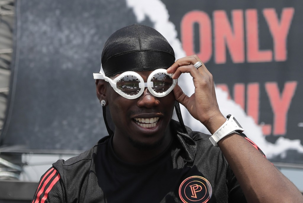 Manchester United's soccer player Paul Pogba, adjusts his goggles, given by a fan, during a meeting with his fans following a media day in Seoul, Sout