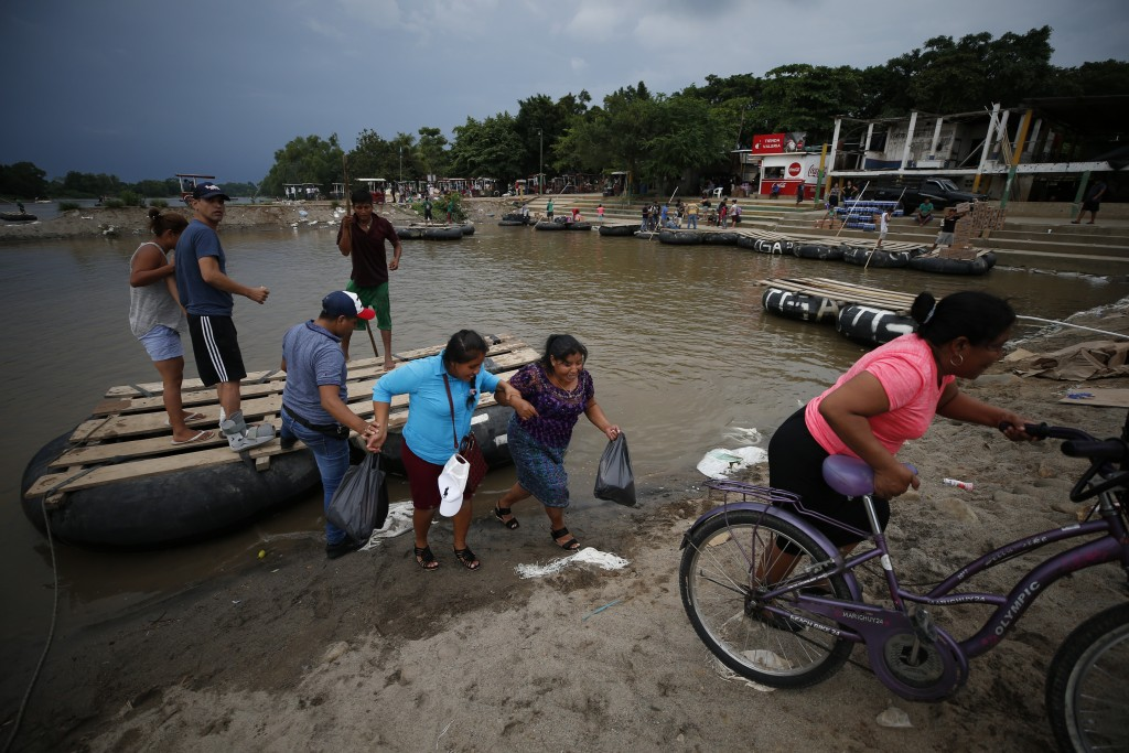Passengers disembark from a raft in Tecun Uman, Guatemala, after crossing the Suchiate River from Mexico, Wednesday, June 12, 2019. Mexican officials