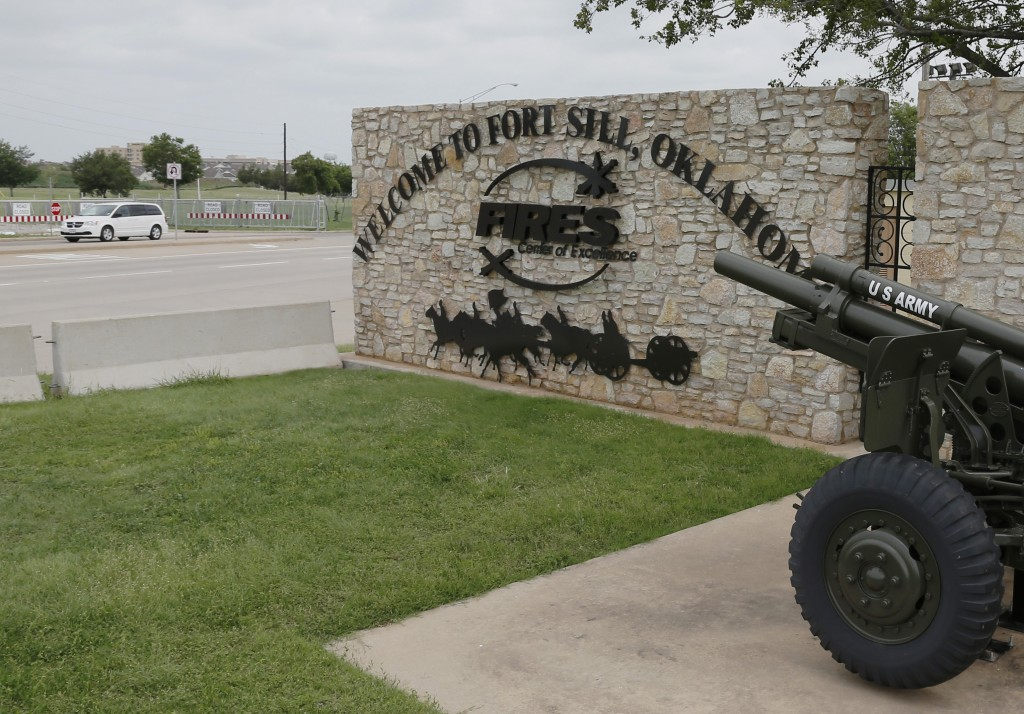 FILE - In this June 17, 2014 file photo, a vehicle drives by a sign at Scott Gate, one of the entrances to Fort Sill, in Fort Sill, Okla. The federal