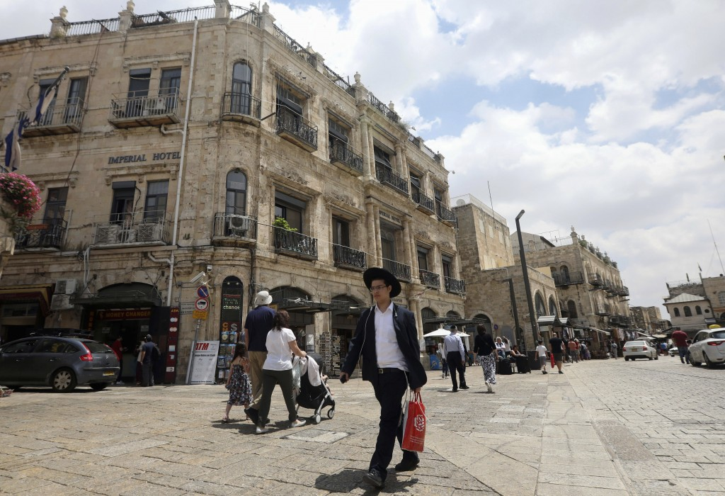 People walk past the Palestinian-run Imperial Hote...