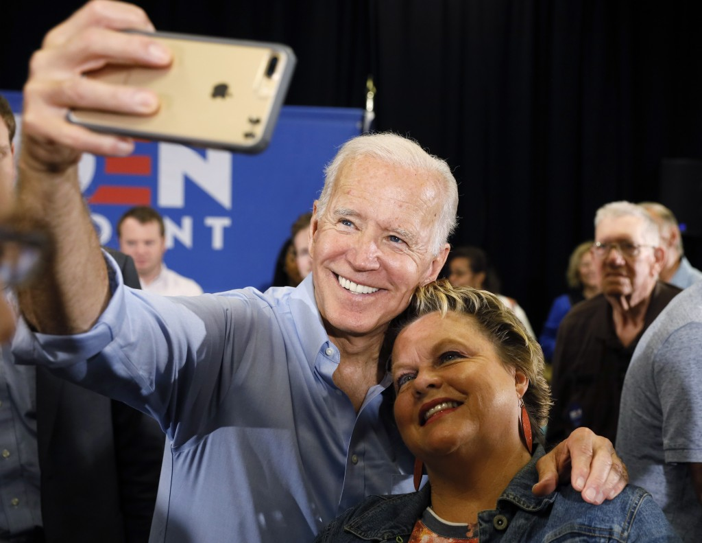 Democratic presidential candidate former Vice President Joe Biden poses for a photo with an audience member after speaking at Clinton Community Colleg