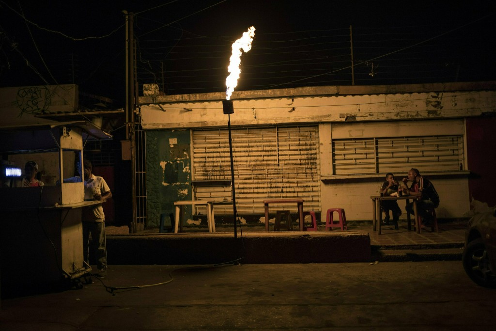 "In this May 23, 2019 photo, Richard Montano eats ""Tumbarrancho"" arepas with his son Reinel Montano, 13, illuminated by a torch known in Maracaibo as a"
