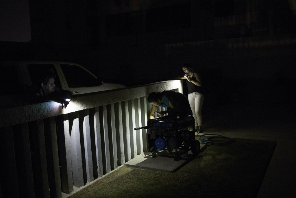 In this May 23, 2019 photo, Yoleida Castro tries to start her newly purchased generator, during a black out in Maracaibo, Venezuela. Millions of poor
