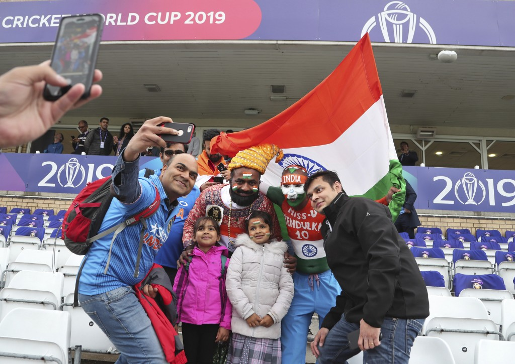 Indian fans pose for photographs as rain delayed start of the Cricket World Cup match between India and New Zealand at Trent Bridge in Nottingham, Eng