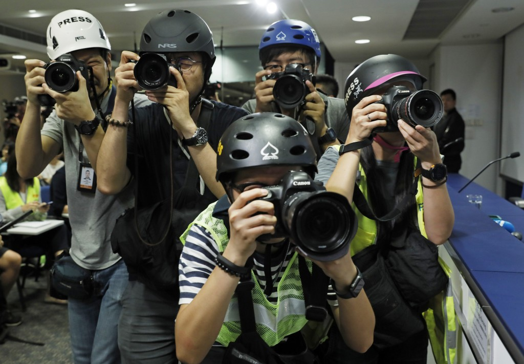 Press photographers wearing helmets for protection in the clashes seen in recent protests, photograph a press conference by Commissioner of Police Ste...