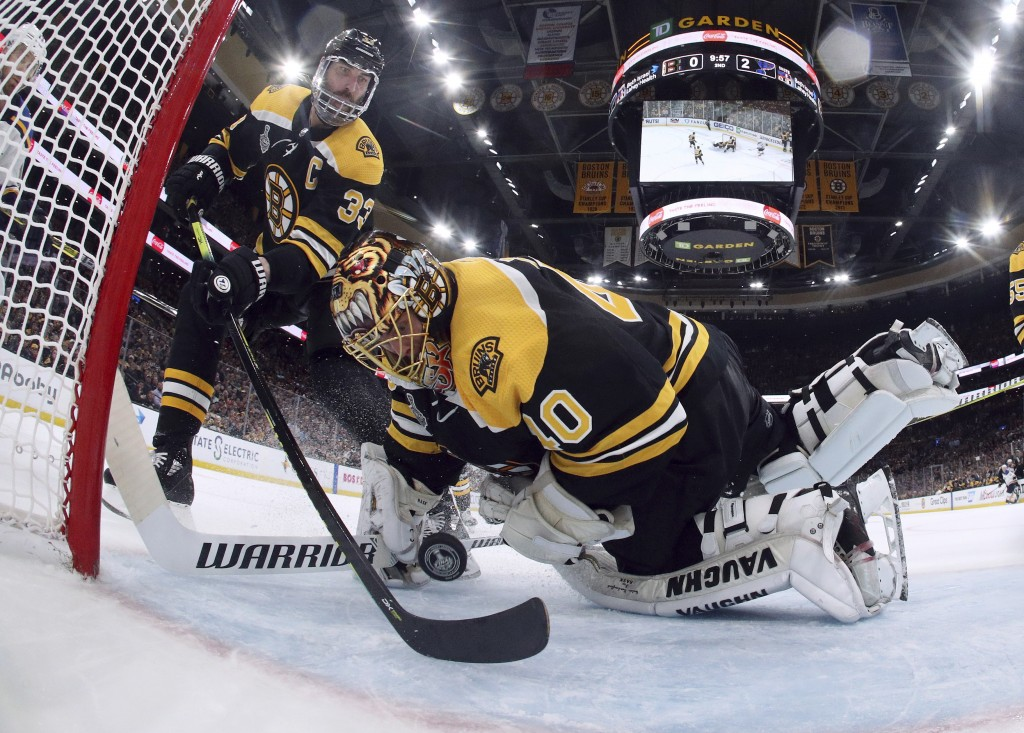 Boston Bruins' Zdeno Chara, left, of Slovakia, reaches behind goaltender Tuukka Rask, of Finland, to keep the puck from crossing the goal line during
