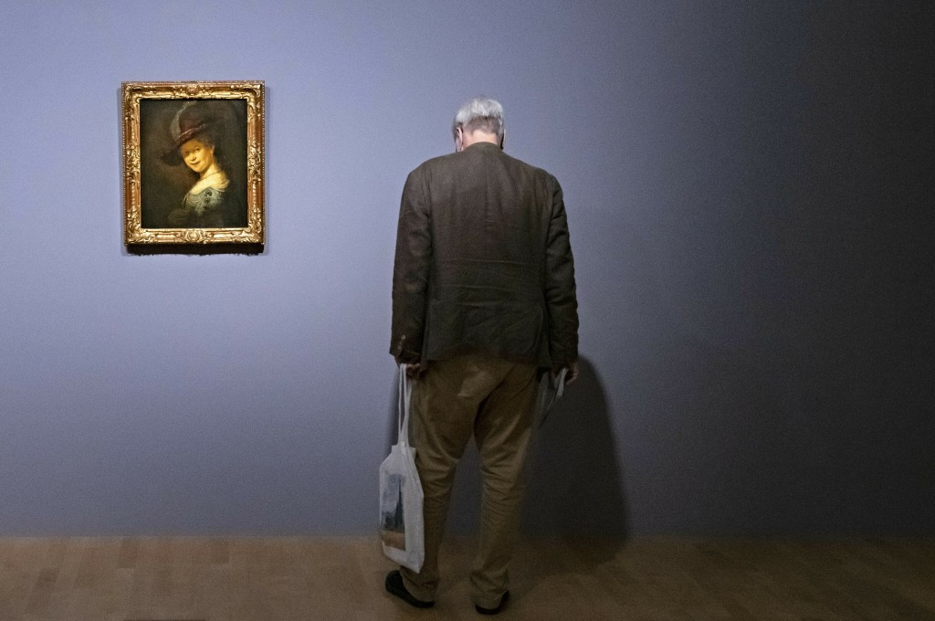 A visitor stands besides the painting 'Bust of a young woman smiling (Saskia van Uylenburgh)' (1633) by Rembrandt during a press preview of the exhibi