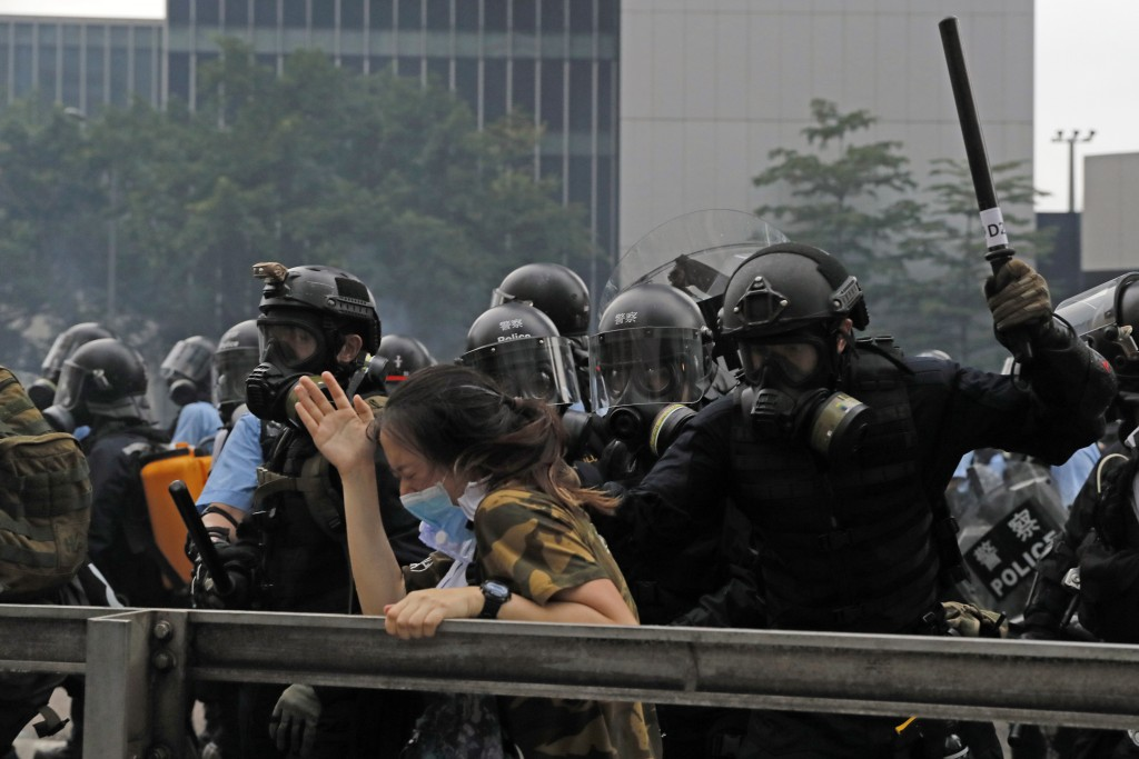 In this photo taken on Wednesday, June 12, 2019,a protester reacts as she is tackled by a riot police officer near the Legislative Council in Hong Kon