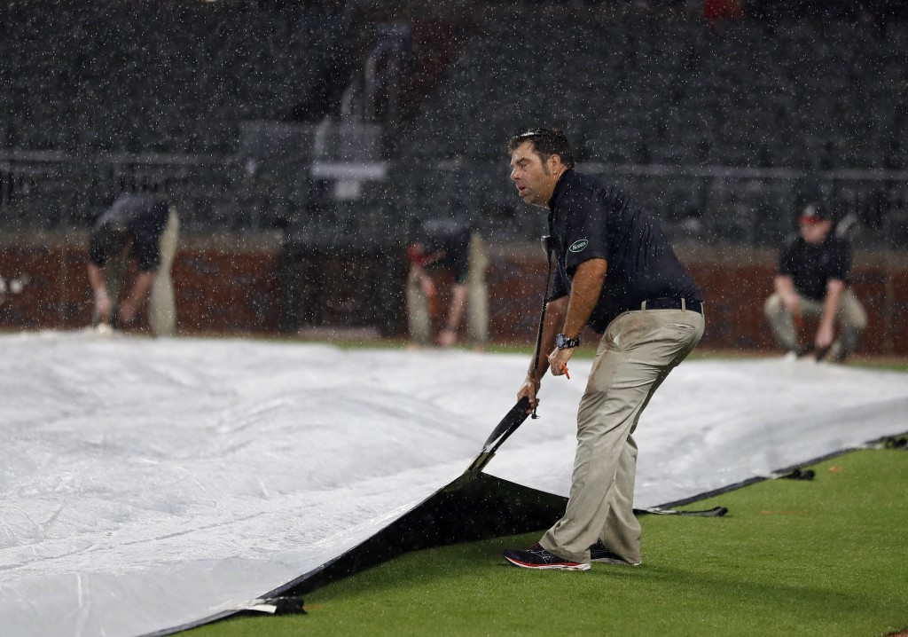 Members of the Atlanta Braves ground crew work to cover the infield during a rain delay in seventh inning of a baseball game between the Braves and Pi...