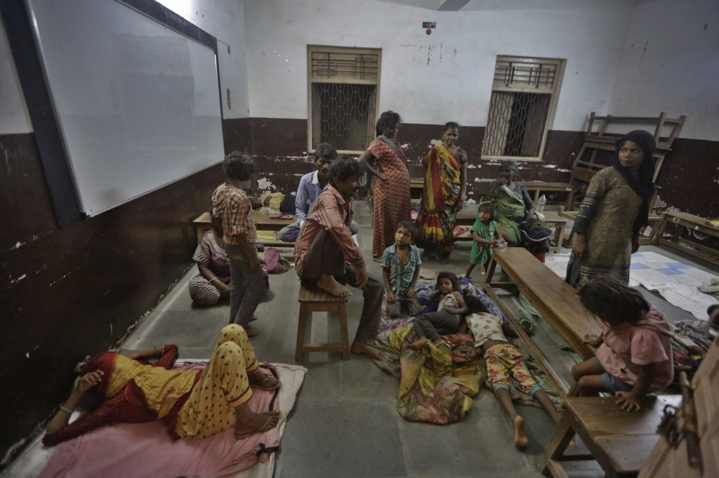 In this Wednesday, June 12, 2019 photo, people evacuated from the coastal areas take shelter at a school in Veraval, Gujarat, India. Authorities have