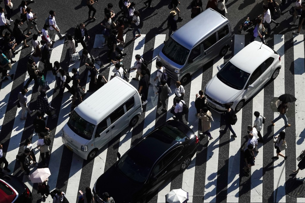 Pedestrians walk across the famous Shibuya crossing as vehicles are stuck in traffic Thursday, June 13, 2019, in Tokyo. It's not just a crossing. Loca