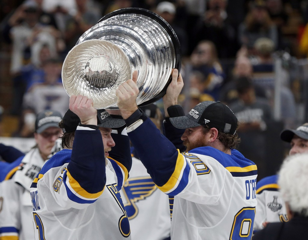 St. Louis Blues' Ryan O'Reilly, right, hands the Stanley Cup to Vladimir Tarasenko, left, of Russia, after the Blues defeated the Boston Bruins in Gam...
