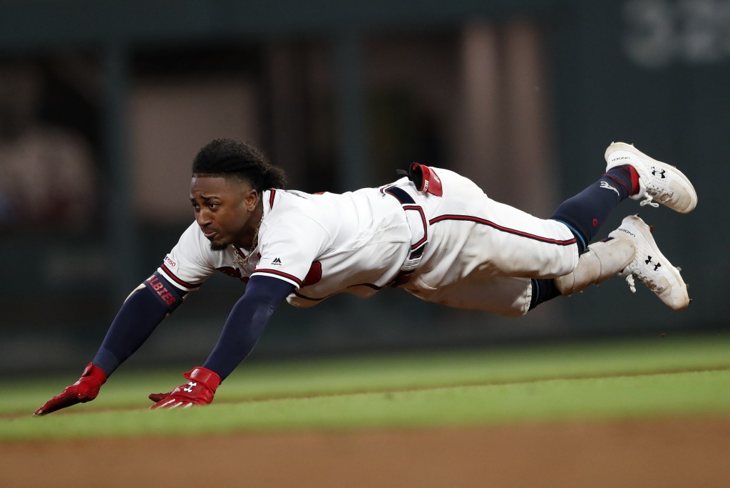 Atlanta Braves' Ozzie Albies dives into second base with a double during the fifth inning of the team's baseball game against the Pittsburgh Pirates o...